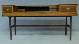 An early 20th century mahogany converted piano writing desk raised on stretchered square supports.