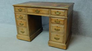 A late 19th century oak pedestal desk with leather inset top above an arrangement of nine drawers