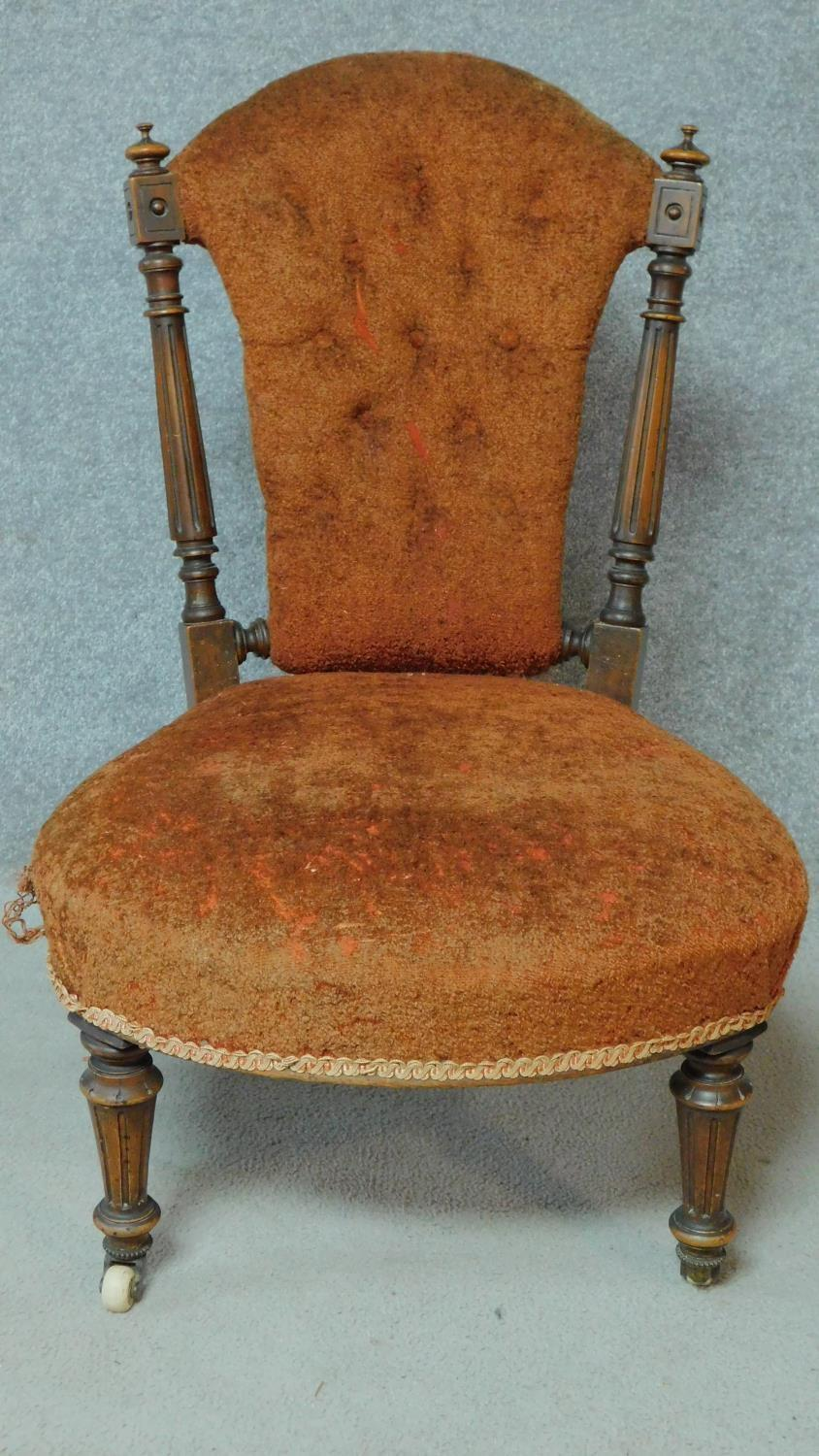 A late 19th century walnut framed buttoned back nursing chair on turned tapering supports. H.82cm