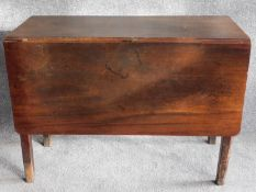A Georgian mahogany drop flap dining table on square section supports.