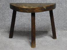 An antique oak three legged milking stool.