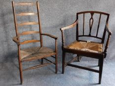 An antique beech ladder back rush seated armchair and a similar oak chair. H.102cm