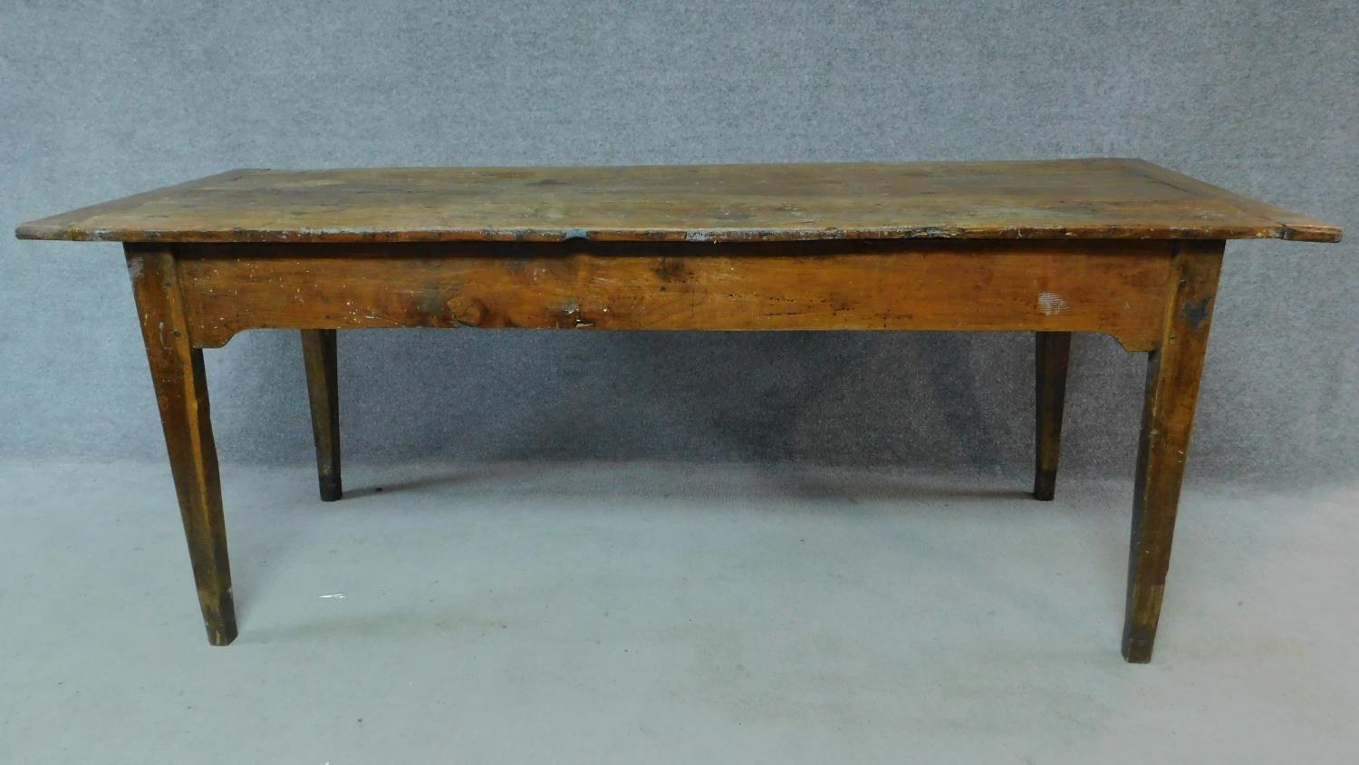 An antique oak planked top refectory dining table with cleated ends and twin end drawers on square