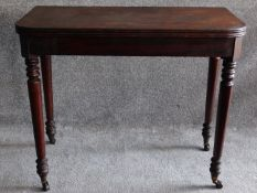 A 19th century mahogany foldover top tea table on turned tapering supports. H.74 W.45 D.92cm