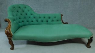 A Victorian rosewood framed chaise longue in buttoned back upholstery on carved cabriole supports.