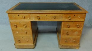 A 19th century oak leather top desk with central long frieze drawer and eight short drawers. H.75
