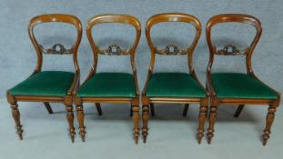 A set of four Victorian mahogany balloon back dining chairs on turned tapering supports. H.87cm
