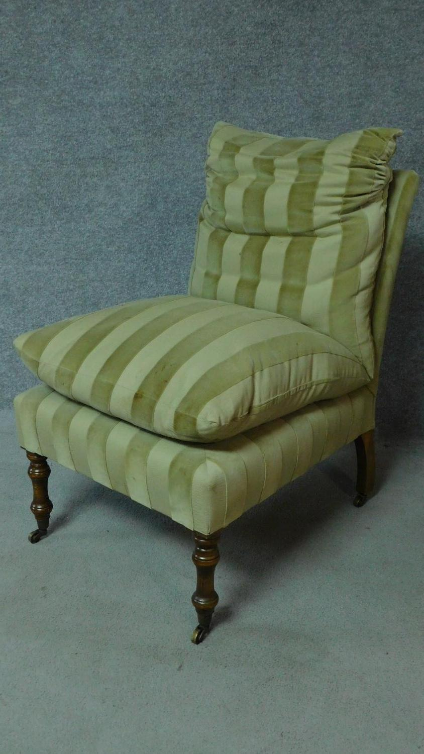 A 19th century style nursing chair in striped upholstery on turned tapering supports. H.87cm
