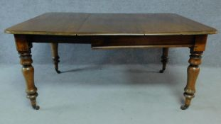 A Victorian mahogany extending table on turned tapering supports terminating on brass cup casters.