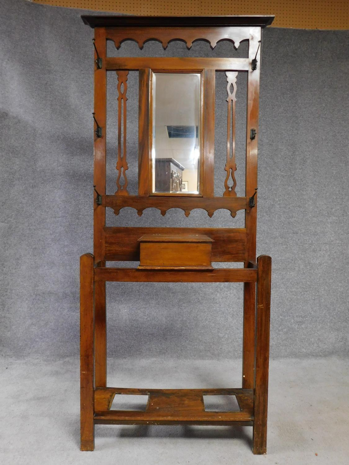 A 19th century Art Nouveau walnut hallstand with central mirror above glove compartment with