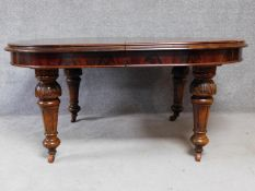 A Victorian figured mahogany extending dining table on turned tapering fluted supports terminating