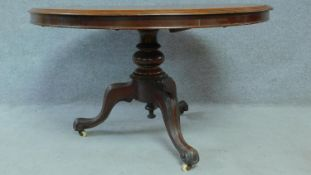 A Victorian mahogany circular dining table with tilt top action raised on carved tripod supports.