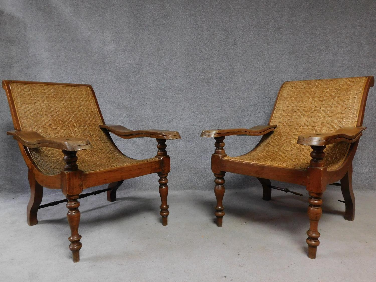 A pair of Colonial teak framed reclining planter's chairs with foldout foot rests on turned tapering
