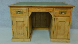 A 19th century pitch pine desk with leather top and two short drawers over panel doors enclosing