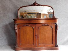 A Victorian mahogany chiffonier with well carved arched mirror above frieze drawer and panel doors