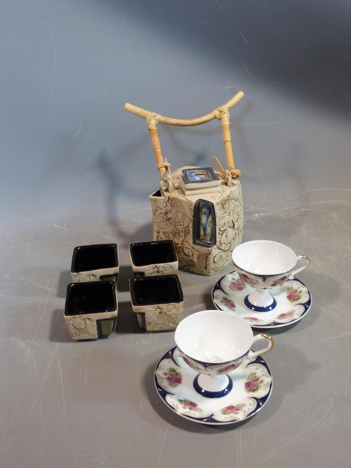 A ceramic Malaysian tea set and a pair of porcelain tea cups and saucers. The tea cups have a