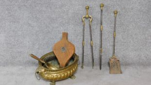 A Victorian repousse brass coal bucket on four lion paw feet and with lion head handles either