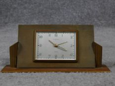 An Art Deco brass desk clock by Europa. Luminous numbers. Geometric form with linear detailing. H.