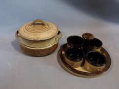 a studio pottery lidded pot and ramakin holder. The lidded two handled pot has an impressed cross