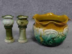 Two painted green ceramic miniature jardineres on column stands and an Art Nouveau floral design