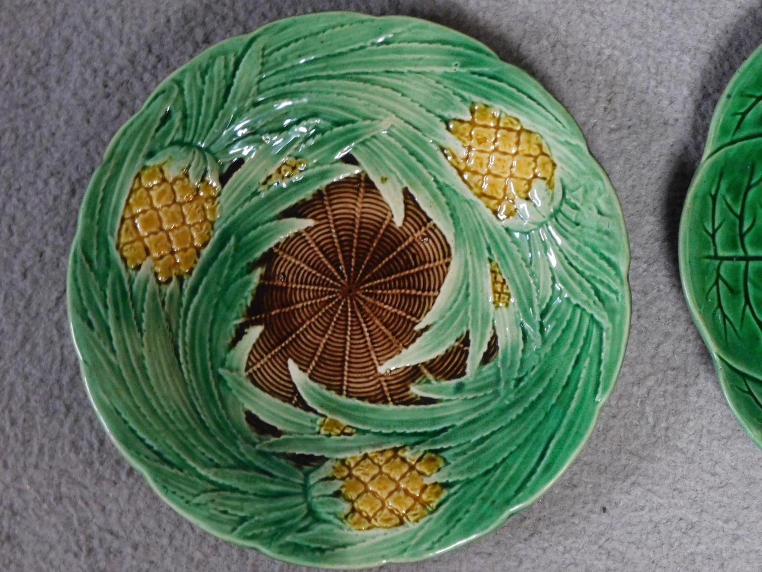 Four antique majolica plates. One designed by George Jones of pineapples in a basket, the waterlilly - Image 6 of 10