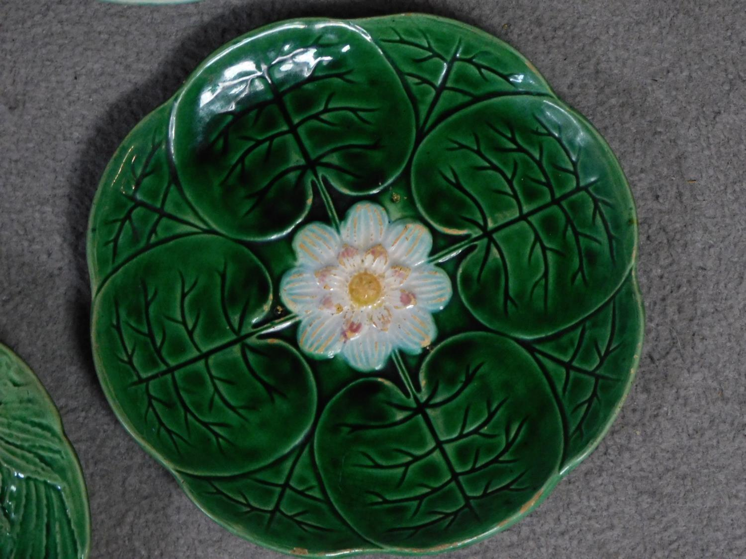 Four antique majolica plates. One designed by George Jones of pineapples in a basket, the waterlilly - Image 4 of 10