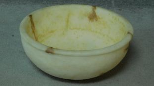 A carved alabaster lipped bowl. H.16 W.45 D.45cm