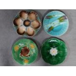 Four antique majolica plates. One designed by George Jones of pineapples in a basket, the waterlilly