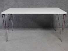 A folding trestle table on chrome supports. H.74 L.140 W.71cm