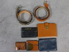 A collection of vintage leather travel and money wallets and two belts. One belt is ostrich and