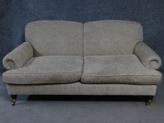 A Victorian style two seater settee on turned supports on brass cup casters. H.85 W.190 D.90cm