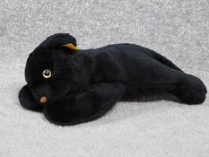 A Steiff vintage toy of a young black panther. With label and gold button. Plastic eyes. W.31cm