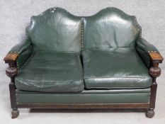 A mid 20th century carved oak frame leather upholstered two seater sofa on bulbous reeded
