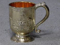 A Corbell and Co silver plated and gilded tankard with repousse floral design and scrolling