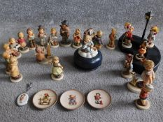 A collection of twenty one German Hummel hand painted figures and wooden display stand with
