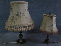 A pair of antique solid brass table lamps, one with a triangular base on three feet and one with a