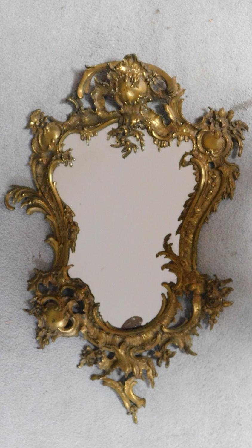 A Rococo style ormolu gilt brass mirror. Rocaille formed frame with wooden back. H.80xW.51cm