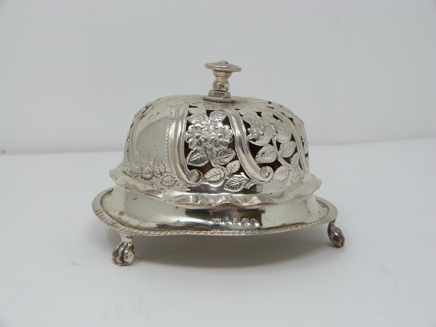 A Victorian silver pierced desk bell with stylised floral design and stylised four petal flower to