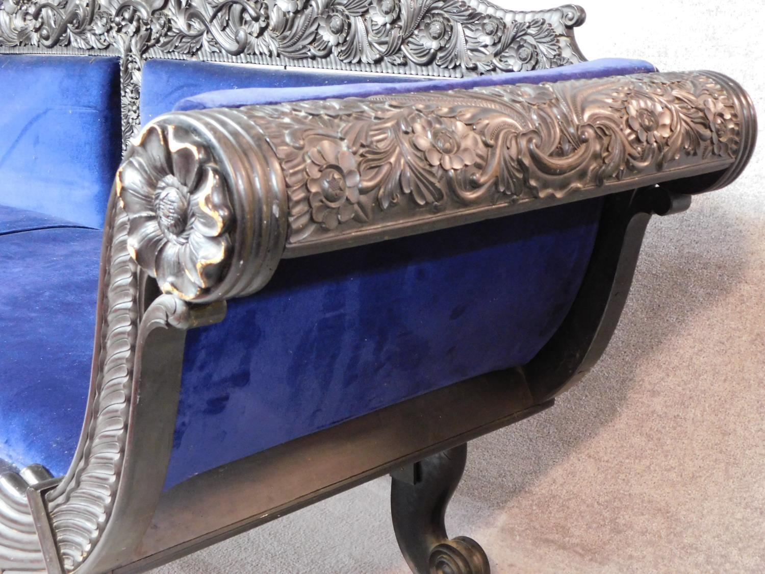 A 19th century Anglo Indian carved ebonised scroll end sofa with blue velvet upholstery on scroll - Image 8 of 9