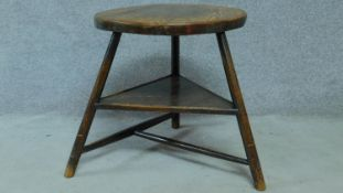 An antique elm circular topped cricket table on three circular section splayed supports united by