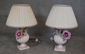 A pair of relief hand painted ceramic urn and flower table lamps on square bases. H.65x45cm