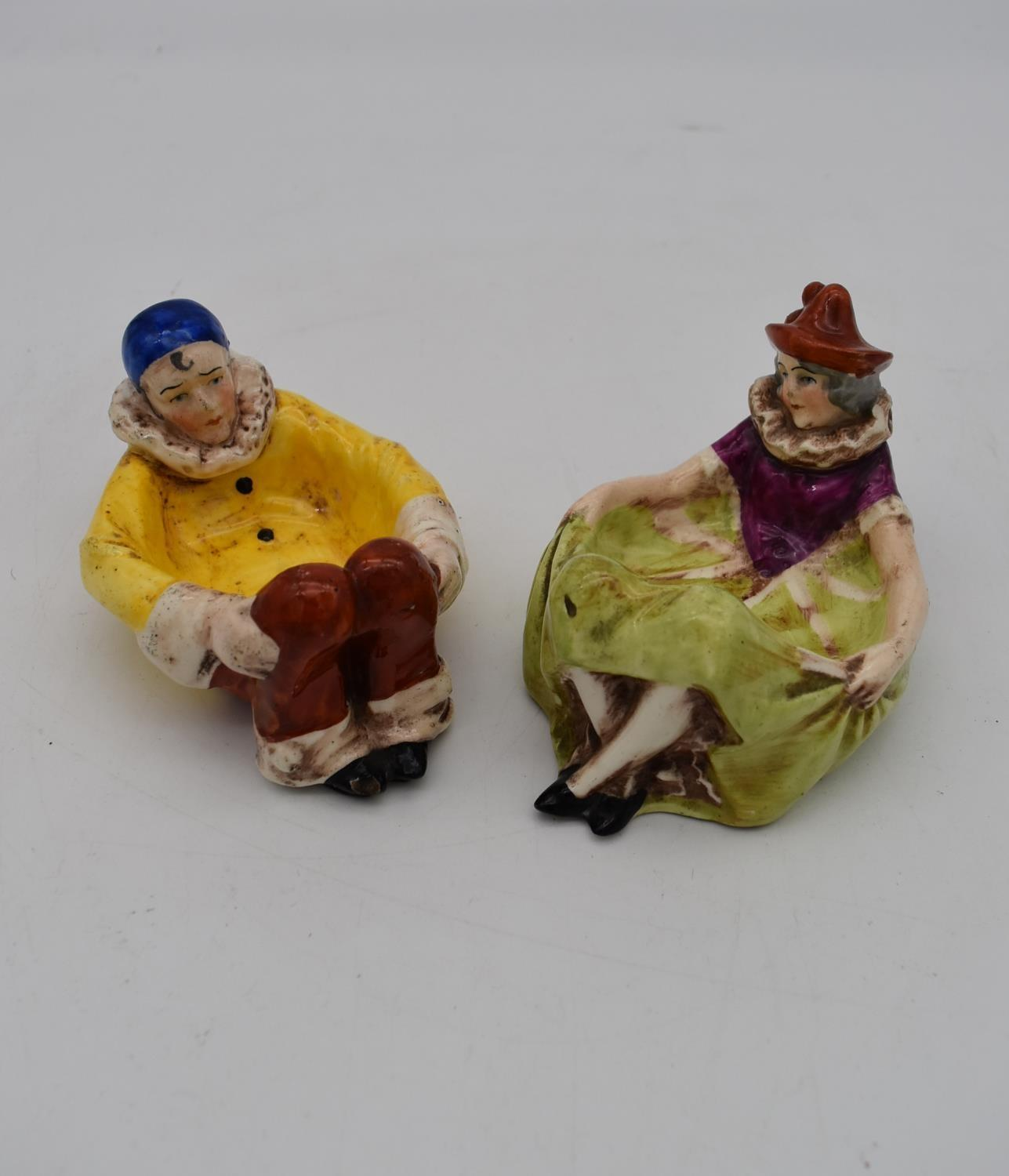 Two antique hand painted porcelain lying figures, one male clown and a female clown, used as dishes.