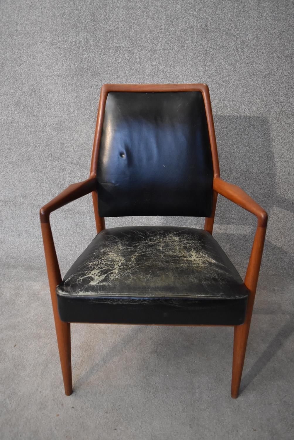 A mid 20th century vintage Danish teak framed armchair in leather upholstery. H.98x60cm