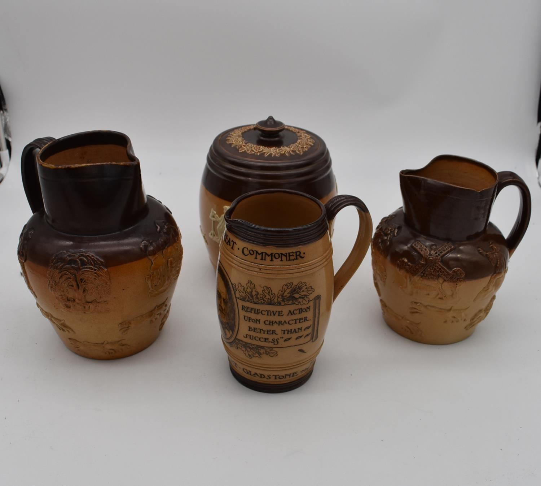 An antique Royal Doulton tobacco jar along with three antique salt glaze earthenware jugs. H.25cm