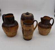 An antique Royal Doulton tobacco jar along with three antique salt glaze earthenware jugs. H.25cm