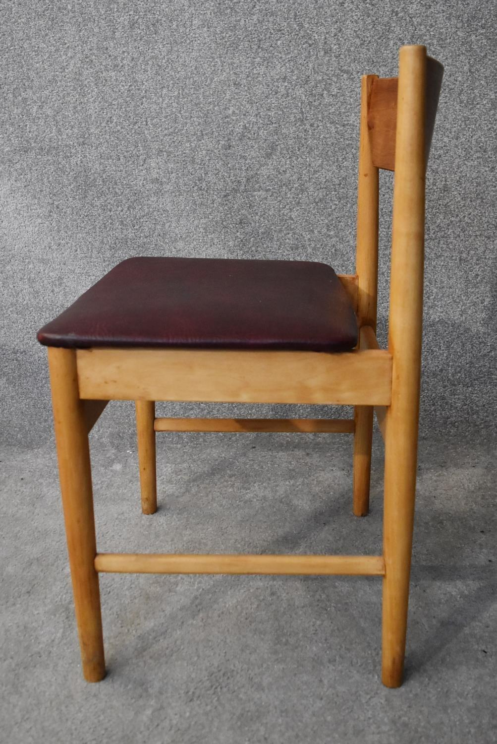A set of four mid 20th century teak dining chairs in faux grained leather burgundy upholstery H. - Image 2 of 4