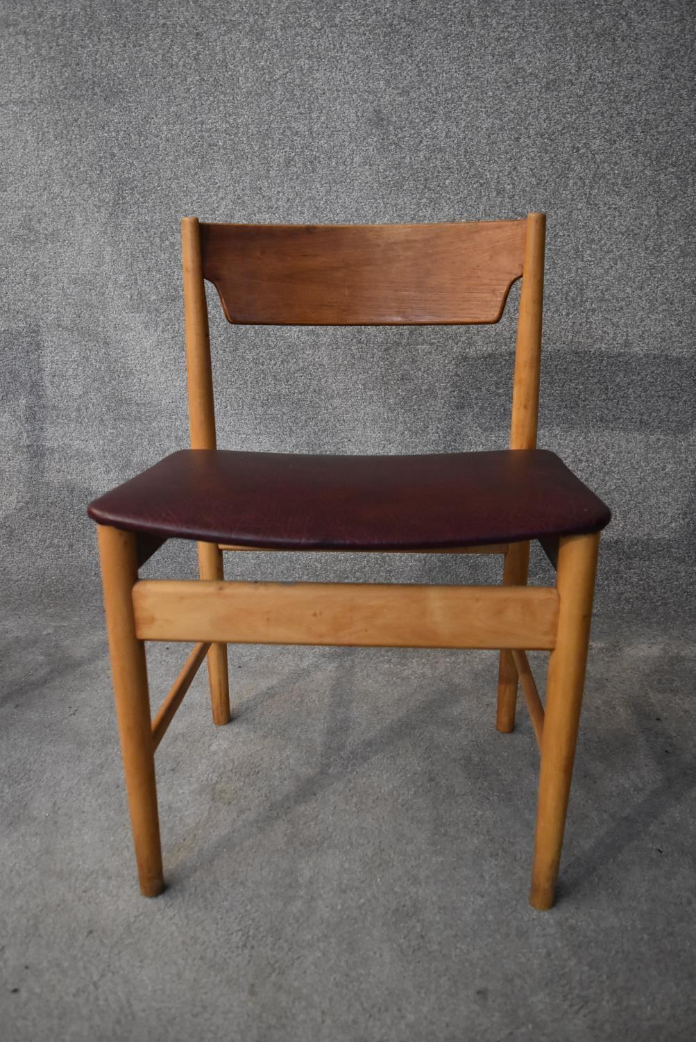 A set of four mid 20th century teak dining chairs in faux grained leather burgundy upholstery H. - Image 3 of 4
