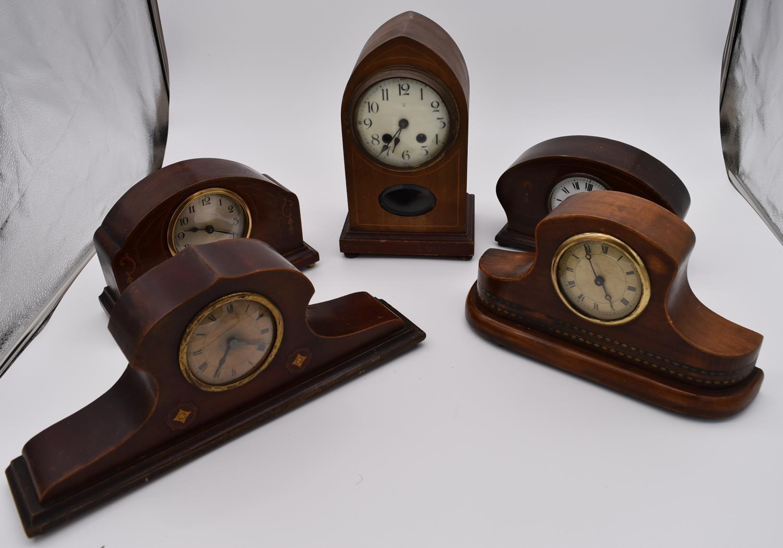 An Edwardian mahogany and satinwood inlaid lancet mantel clock and four other Edwardian mantel