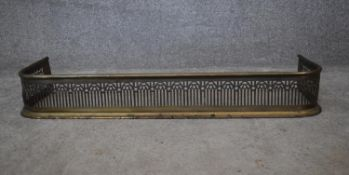 A 19th century pierced brass fire kerb. H.14x92x35cm