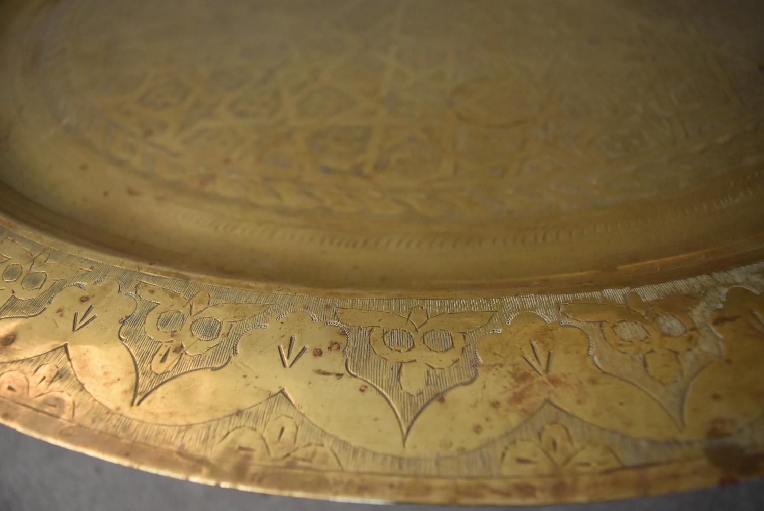 An Eastern brass topped table on folding hardwood stand. H.45xDia.90cm - Image 3 of 5